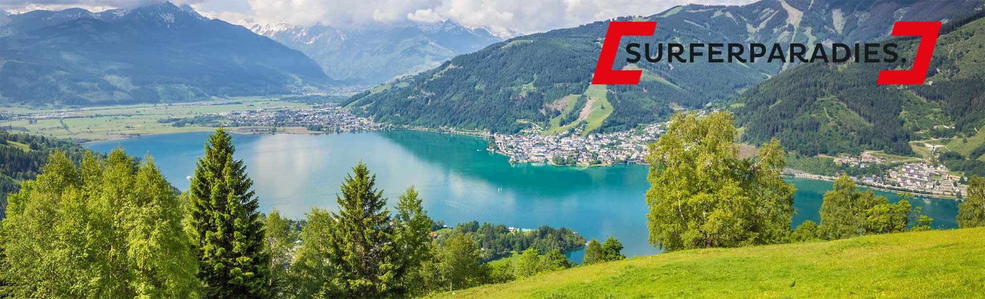 Panoramic view of beautiful scenery in the Alps with clear lake and green meadows full of blooming flowers on a sunny day with blue sky and clouds in springtime, Zell am See, Salzburger Land, Austria.